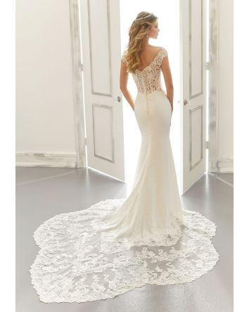 This sheath wedding dress in crepe and lace has cap sleeves and a v-neck neckline.  Wedding Dress Details:  Dress Style #2184 Anya  Size: 12 (Sample Dress in Stock)  Color: Ivory/Honey (pictured)  Silhouette:Sheath  Neckline: V-neck  Slee